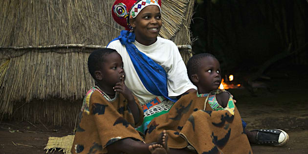 Zulu woman in traditional red headdress of a married woman with her children. Beehive hut in the background. Lesedi Cultural Village near Johannesburg, South Africa.