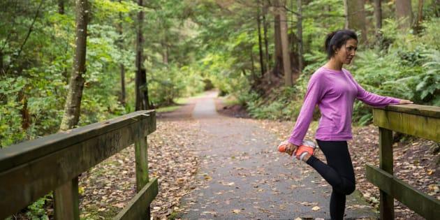 Woman stretching leg preparing for run in woods