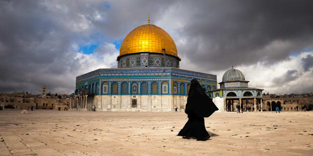 Muslim woman walking by the Dome of the Rock in Jerusalem.