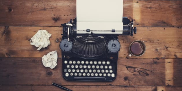 Top view thirties retro writers desk with typewriter on old wooden background table top.