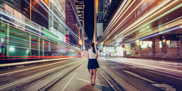 Young woman is lost in metropolitan city at night, Hong Kong.