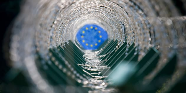 Concept image of a tunnel made of barbed wire and European Union flag at the end of the tunnel