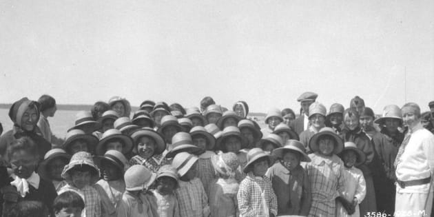 Students assemble in formal attire outside the Fort Resolution Indian Residential School in Fort Resolution, N.W.T. in a 1928 archive photo.