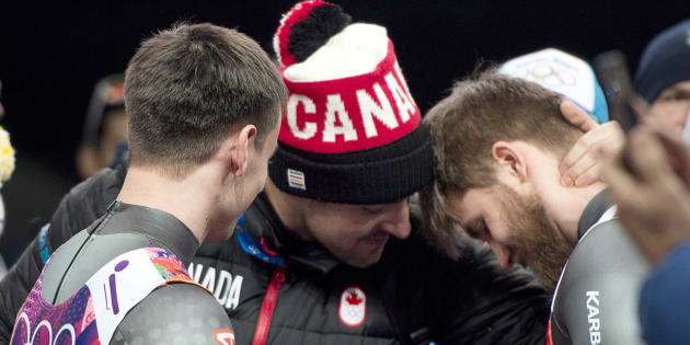 Canadian luge athlete Sam Edney, centre, consoles Canadian doubles luge pilot Tristan Walker as teammate Justin Snith looks on after their fourth-place finish in the Men's Doubles Luge at the Sochi Winter Olympics in Krasnaya Polyana, Russia, Wednesday, Feb. 12, 2014.