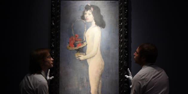 """Asistentes de galería colocando la obra """"La fillette à la corbeille fleurie"""" de Picasso."""