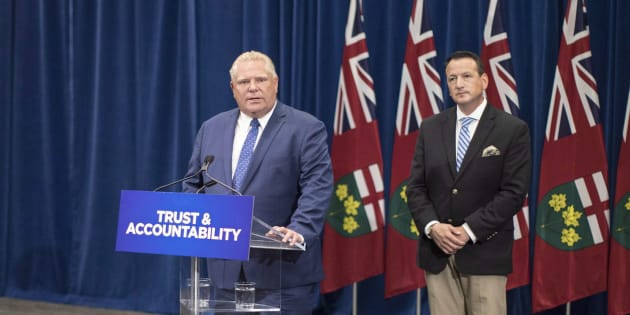 Ontario Premier Doug Ford stands with Minister of Energy Greg Rickford as he makes an announcement at Queen's Park in Toronto on Aug. 15, 2018.