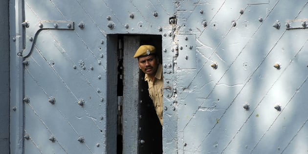 A policeman peers from inside the gate of Chanchalguda jail in Hyderabad.