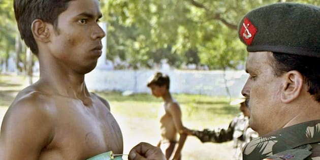 An Indian army officer (R) measures the chest of a youth during a recruitment rally in Bhopal.
