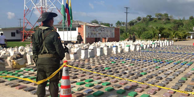 A Colombian national policeman stands guard in front of packages of cocaine, which were confiscated in Turbo province near the border with Panama, May 15, 2016.   Colombian  Police/Handout via REUTERS      ATTENTION EDITORS - THIS PICTURE WAS PROVIDED BY A THIRD PARTY. EDITORIAL USE ONLY