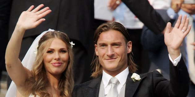 The captain of Italian Serie A football club AS Roma, Francesco Totti (R), waves after his wedding to television personality Ilary Blasi (L) in the church of Santa Maria dell'Aracoeli in Rome June 19, 2005. REUTERS/Tony Gentile  TG/PN