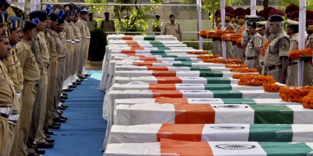 Central Reserve Police Force (CRPF) personnel pay their last respects near the coffins of policemen who died in a Maoist attack, in Raipur, capital of the eastern Indian state of Chhattisgarh June 30, 2010.