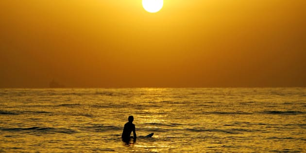 A surfer enjoys a cool surf at sunrise at Sydney's Manly Beach.