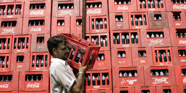 A worker carries a crate of Coca Cola at the local dealer in Jammu.