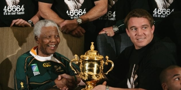 Former South African president Nelson Mandela (L) smiles as he is handed the Webb Ellis Trophy by Springboks  Rugby captain John Smit at the Mandela foundation in Houghton October 27, 2007.