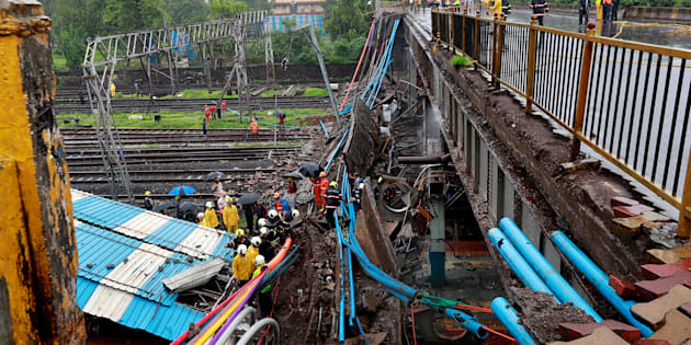 Rescue workers seen working at the site of an overbridge that collapsed over the railway tracks after heavy rains in Mumbai.