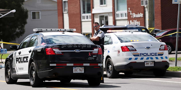 Fredericton Police and Royal Canadian Mounted Police (RCMP) patrol in front of the apartment complex which was the scene of a shooting incident in Fredericton.