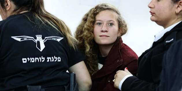 epa06399655 17 year old Palestinian Ahed Tamimi (C), a campaigner against Israel's occupation, appears at a military court at the Israeli-run Ofer prison in the West Bank village of Betunia, 20 December 2017. Reports state that the Israeli army arrested Tamimi on 19 December 2017, after a video was posted of her slapping Israeli soldiers in the occupied West Bank as they remained impassive.  EPA/ABIR SULTAN