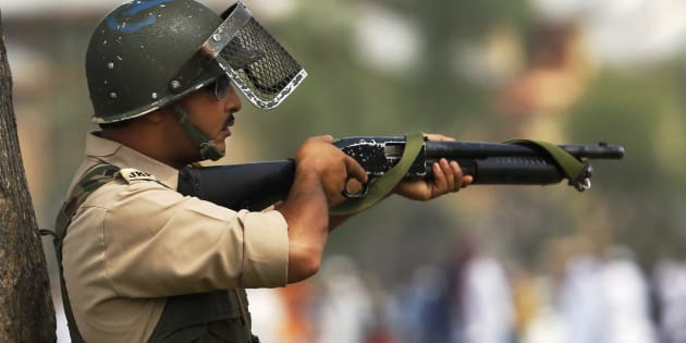 A policeman aim his pellet gun at protesters during a protest in Srinagar, Indian controlled Kashmir, Wednesday, July 6, 2016.