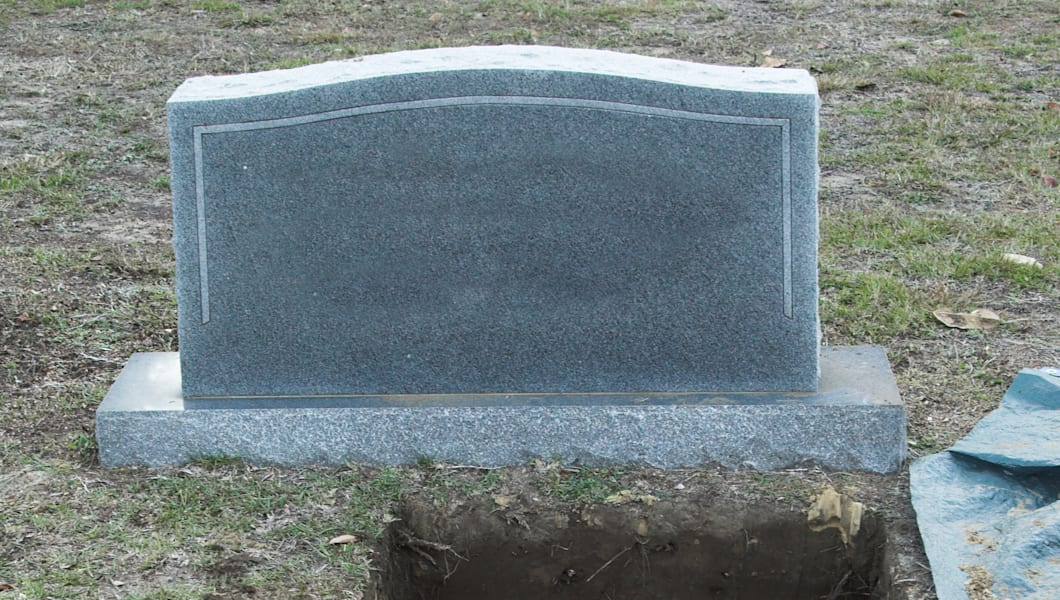 open grave with blank tombstone