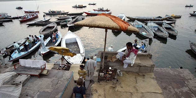 FILE PHOTO: Tourists board a boat, as a Hindu priest looks on, at the Dashashumedh ghat on the banks of the Ganga river in Varanasi, 09 March 2006.
