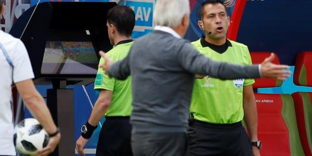 Andres Cunha observa o monitor de vídeo para, na sequência, reverter sua decisão e marcar pênalti a favor da França.
