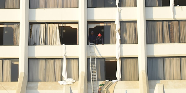 Pakistani fire fighters look from a room of Regent Plaza Hotel following a fire in the Pakistan's port city of Karachi on 5 December, 2016.