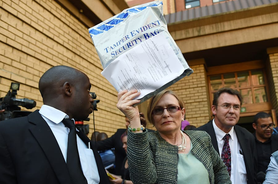 """Helen Zille, then DA leader, outside the High Court in Pretoria on September 4, 2014, with the evidence bag containing the so-called """"spy tapes""""."""