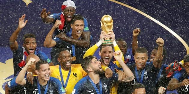 France's Hugo Lloris lifts the trophy as his team celebrates winning the World Cup in Moscow on Sunday night.
