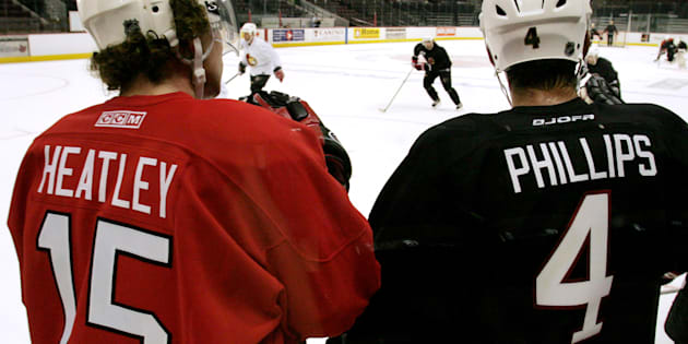 Then-Ottawa Senators Dany Heatley (L) and Chris Phillips watch their teammates during the second day of training camp in Ottawa September 14, 2005.