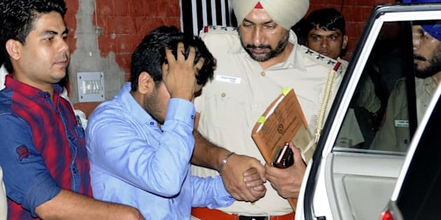 Vikas Barala (in blue shirt) being taken into Chandigarh police custody at Sector 26 Police Station.