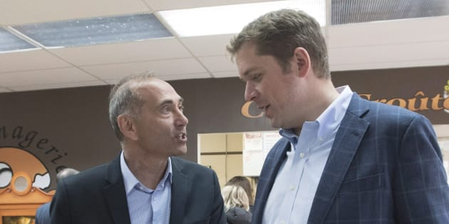 Conservative Leader Andrew Scheer and Saguenay-Le Fjord candidate Richard Martel chats as they carry food at the famous Boivin cheese counter on June 14, 2018 in Saguenay, Que.