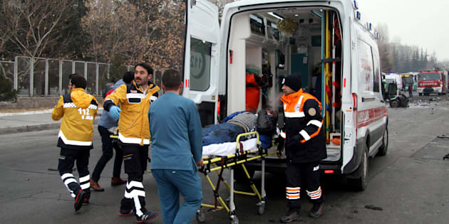 TURKEY OUT This picture obtained from the Ihlas News Agency shows a police officer and people walking next to the wreck of public bus following an explosion on December 17, 2016 in Kayseri, central Turkey. Several people were wounded on December 17 in a car bombing close to the public bus in the central Turkish city of Kayseri, television reports said. The Dogan news agency said that the blast took place opposite the Erciyes University in the city. NTV television said there could be fatalities as a result of the blast. The state-run Anadolu news agency said that the bus was owned by the municipal transport authorities in Kayersi but was transporting Turkish soldiers who had taken permission to go to a local market for the day. / AFP / IHLAS NEWS AGENCY / IHLAS NEWS AGENCY / Turkey OUT        (Photo credit should read IHLAS NEWS AGENCY/AFP/Getty Images)