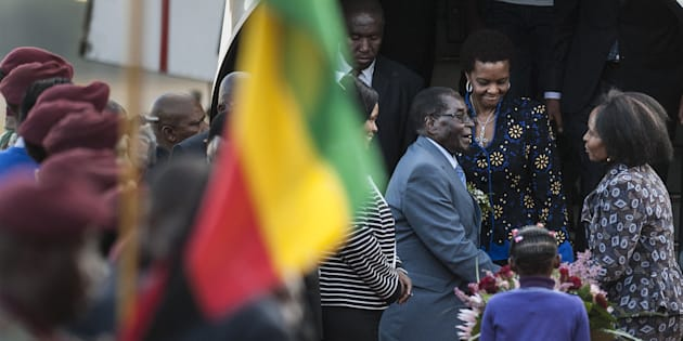Zimbabwe's President Robert Mugabe (3rd R) and his wife Grace (2nd R) are greeted by South African Minister of International Relations and Cooperation Maite Nkoana-Mashabane (R) upon their  arrival at the Waterkloof Air Force base in Pretoria on April 7, 2015, for an official state visit.