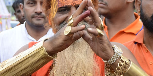 GHAZIABAD, INDIA - JULY 28: 54-year-old Sudhir Makkar, who is popularly known as Golden Baba, wears nearly 12.5 kg of gold during Kanwar Yatra on July 28, 2016 in Ghaziabad, India.