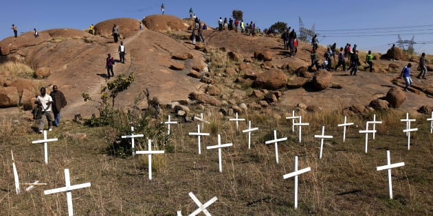 """Members of the mining community walk near crosses placed at a hill known as the """"Hill of Horror"""", where 43 miners died during clashes with police last year, during a strike at Lonmin's Marikana platinum mine in Rustenburg, 100 km (62 miles) northwest of Johannesburg, May 14, 2013. South African workers of world No. 3 platinum producer Lonmin launched a wildcat strike on Tuesday, halting all of the company's mine operations and reigniting fears of deadly unrest that rocked the industry last year. The platinum belt towns of Rustenburg and Marikana, which saw violent strikes at Lonmin and other platinum producers last year, are a flashpoint of labour strife with tensions running high over looming job cuts and wage talks."""