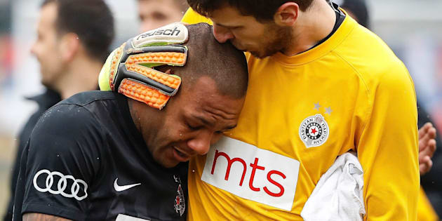 Partizan Belgrade's goalkeeper Filip Kljajic (R) hugs Brazilian midfielder Everton Luiz as he leaves the field in tears on February 19, 2017, at the end of a Serbian championship match between Partizan and Rad, after racist remarks from Rad's supporters, Serbian television B92 reported. Every time he touched the ball, 28-year-old Everton Luiz was being monkey-screamed from a group of supporters of Rad Belgrade, the source said. Shortly before the end, the match was briefly interrupted when Rad supporters also waved a banner with an insulting message against the Brazilian.  / AFP / STR        (Photo credit should read STR/AFP/Getty Images)