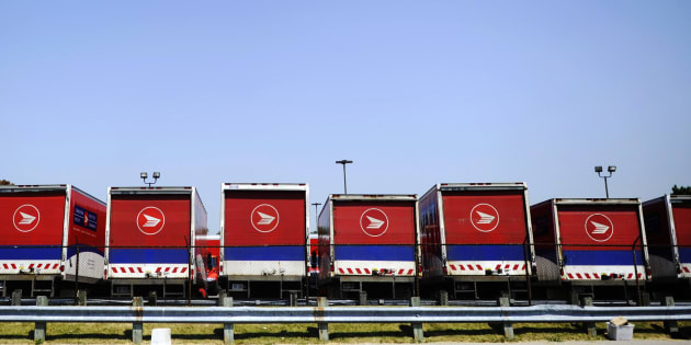 Mail trucks are seen as they are parked behind a fence after the Canadian Union of Postal Workers (CUPW) were locked out at a Canada Post sorting facility in Toronto, June 15, 2011.