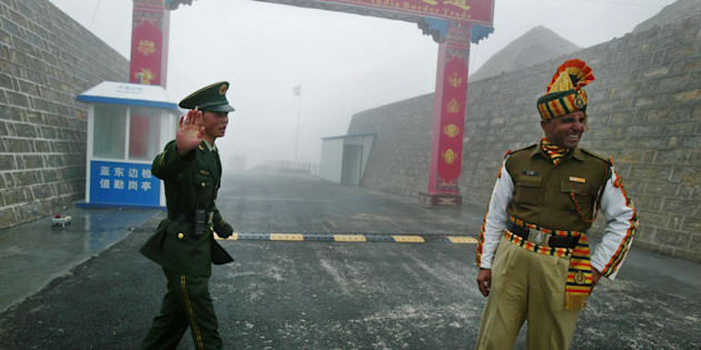 In this photograph taken on July 10, 2008 a Chinese soldier (L) and an Indian soldier stand guard at the Chinese side of the ancient Nathu La border crossing between India and China.
