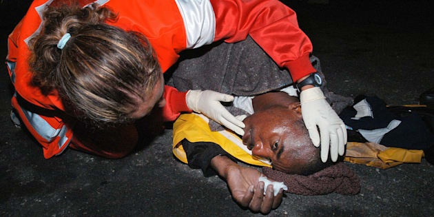 Una miembro de Cruz Roja atiende a un subsahariano llegado al puerto de Arguineguin, Gran Canaria, en una imagen de archivo.