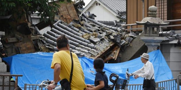 La gente hace una pausa para mirar una casa derrumbada después de un terremoto en la ciudad de Ibaraki, al norte de la prefectura de Osaka este 18 de junio de 2018.