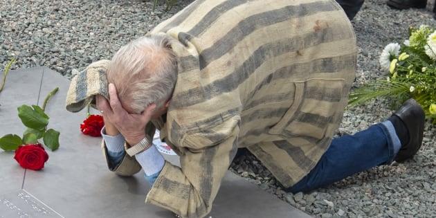 Un survivant pleure sur une plaque de métal lors des cérémonies de commémoration du 73e anniversaire de la libération de l'ancien camp de concentration nazi de Buchenwald, près de Weimar, en Allemagne.