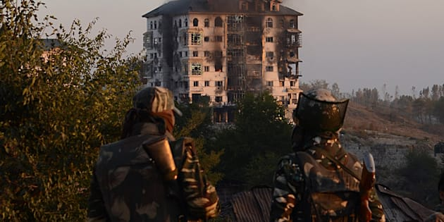 Indian army soldiers look on as smoke rises from the building where suspected militants have taken refuge in Pampore, on the outskirts of Srinagar on 11 October, 2016.