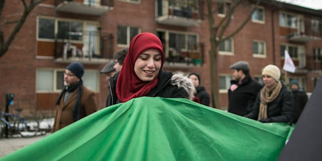 People carry a massive flag during a march against racism and Islamophobia in Montreal, Que., on March 26, 2017.