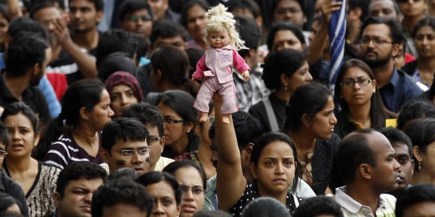 A parent holds high a doll belonging to her child as she participates in a protest against alleged police inaction after a six-year-old was raped at a school, in Bangalore, India, Saturday, July 19, 2014.