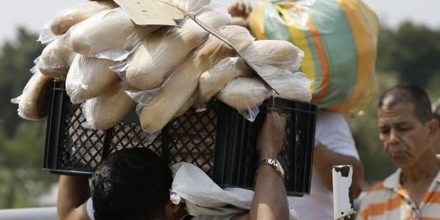 Un hombre venezolano lleva una caja llena de pan de regreso a su país, tras comprarla en La Parada, en las afueras de Cúcuta, Colombia, en la frontera con Venezuela, el lunes 4 de febrero de 2019.