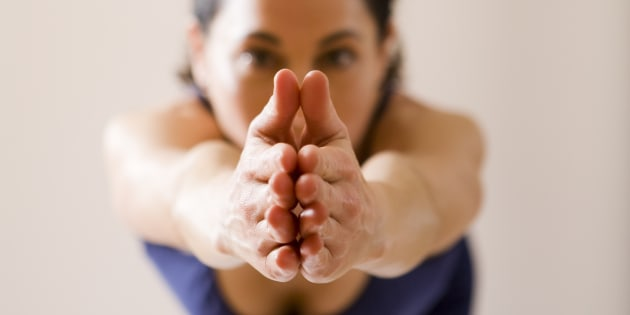 A yoga instructor poses with her hands together.