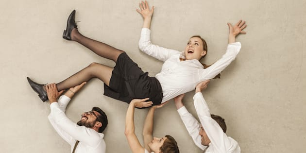Business people carrying businesswoman in office