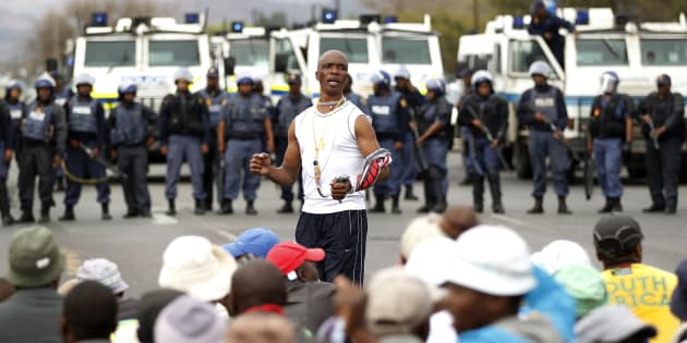 A protester sings as police officers stand guard to prevent marchers from proceeding, in Rustenburg, South Africa's North West Province 16 September 2012.