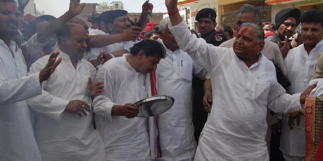 Samajwadi Party (SP) chief Mulayam Singh Yadav (R) waves to his supporters.
