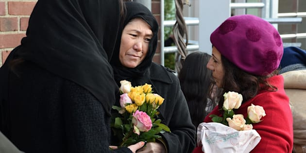 Refugees from Iran hold flowers during a demonstrationagainst violence in Cologne, Germany, on Jan. 22, 2016.